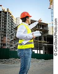 engineer in hardhat and safety jacket checking building site...