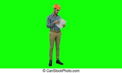 Engineer in hardhat examining construction plan on a Green Screen, Chroma Key.