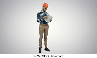 Engineer in hardhat examining construction plan on white...