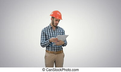 Engineer in hardhat looking at construction plan on white background.