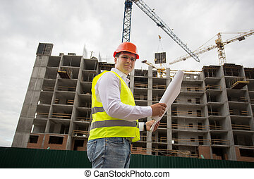 Engineer in hardhat standing on building site and checking blueprints