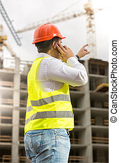Engineer in hardhat talking by phone and pointing at...