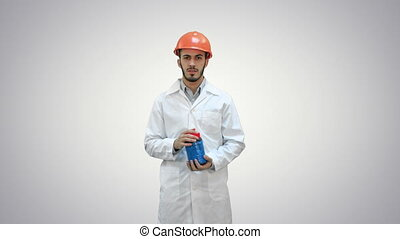 Engineer in helmet and white coat launching demolition on white background.
