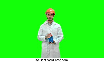 Engineer in helmet and white coat launching demolition on a Green Screen, Chroma Key.