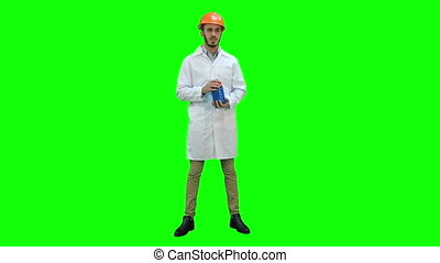 Engineer in helmet and white coat starting building demolition on a Green Screen, Chroma Key.