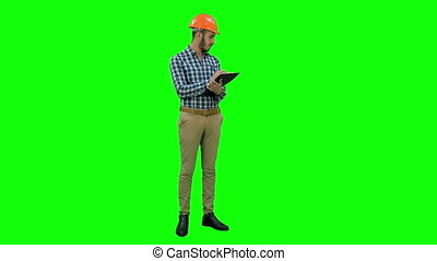 Engineer in helmet inspecting construction site on a Green Screen, Chroma Key.