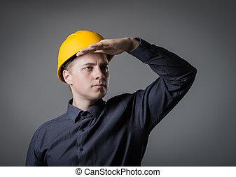 engineer in helmet looks into the distance