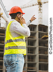 Engineer in red hardhat talking by phone and pointing at...