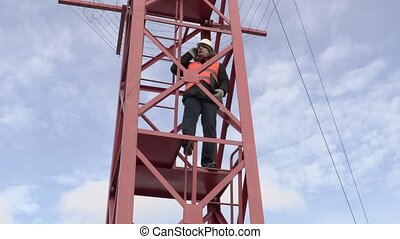 Engineer in the tower talking on smart phone