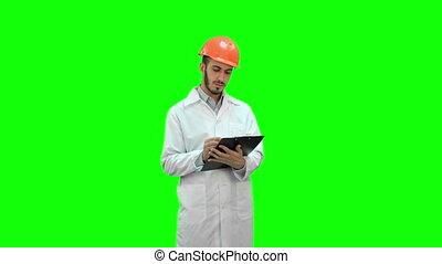 Engineer in white coat preparing report on a Green Screen, Chroma Key.
