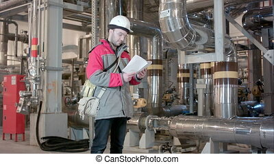 Engineer Inside Power Plant With Checklist. Professional shot on BMCC RAW with high dynamic range. You can use it e.g in your commercial video, corporate, business, presentation, broadcast video.
