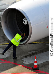 Engineer inspecting aircraft engine