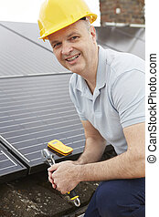 Engineer Installing Solar Panels On Roof Of House