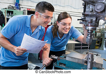 Engineer Instructing Female Apprentice On Use Of Drill