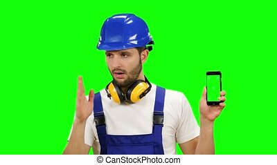 Engineer is holding a phone in his hand and showing his...