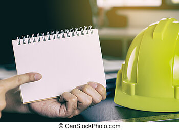 Engineer is pointing at blank paper for copy space