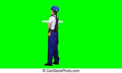Engineer is standing and talking on the phone with a drawing in her hands. Green screen