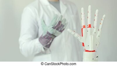 Engineer is testing robotic prosthesis hand which repeats...