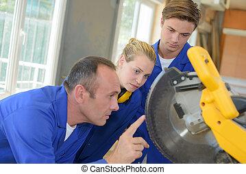Engineer looking at circular blade on machine