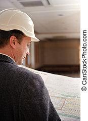 Engineer looking at plans.