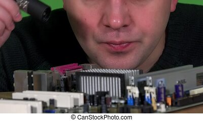Engineer man looking at computer motherboard with flash light