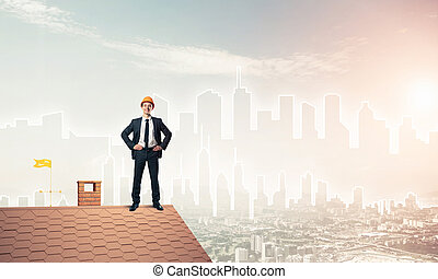 Engineer man standing on roof and looking away. Mixed media
