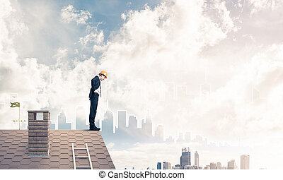 Engineer man standing on roof and looking down. Mixed media