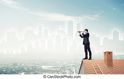 Engineer man standing on roof and looking in spyglass. Mixed...