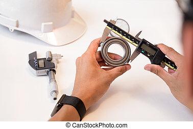 Engineer man using vernier caliper measuring the bearing