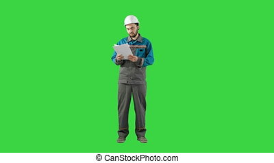 Engineer Man Verify and Read Files Documents on a Green Screen, Chroma Key.