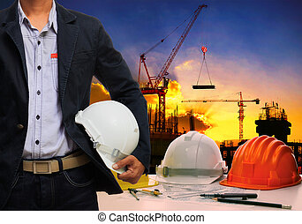 engineer man wit;h white safety helmet standing against working