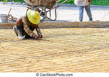 Engineer meshing rebar for flooring with cement.