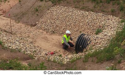 Engineer near flow pipe in deep ditch top view