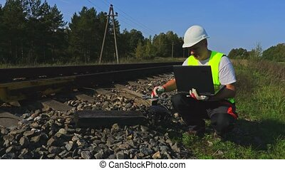 Engineer near railway with laptop check the electronics...