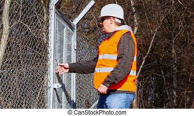 Engineer near to the fence - Engineer with the cell phone...