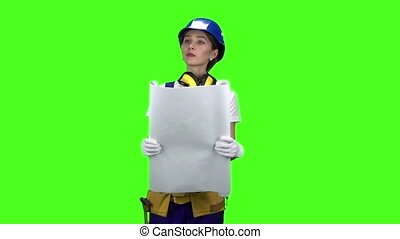 Engineer of the construction site carries a drawing. Green...