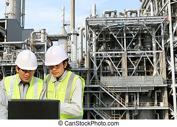 engineer oil refinery discussion with laptop on location...