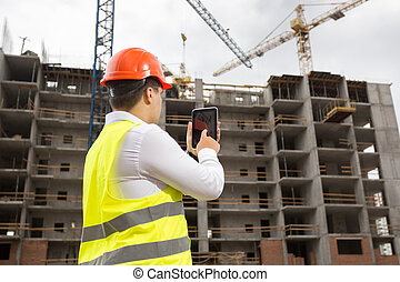 Engineer on building site with digital tablet