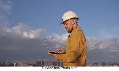 Engineer on construction site using laptop at urban city