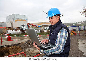 Engineer on construction site with laptop computer