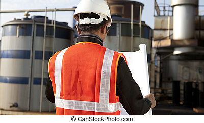 engineer on location site with blueprint