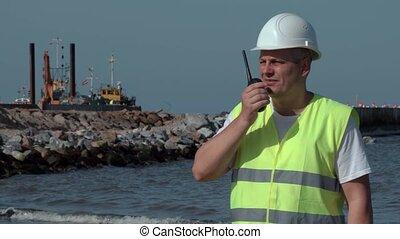 Engineer on walkie talkie on the seaside