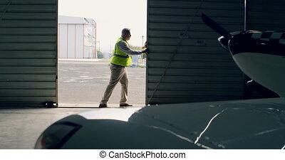 Engineer opening hangar gate at aerospace hangar 4k