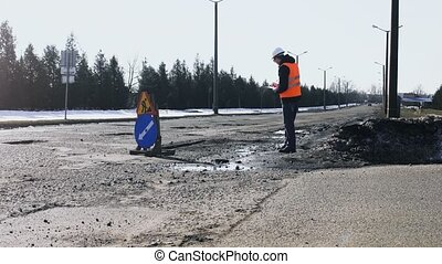 Engineer or builder looks, inspects the road pits and writes...