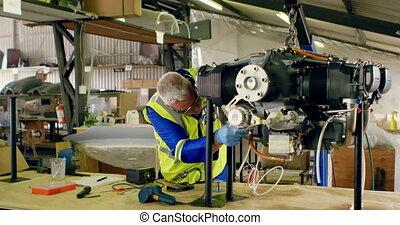 Engineer repairing aircraft engine in hangar 4k