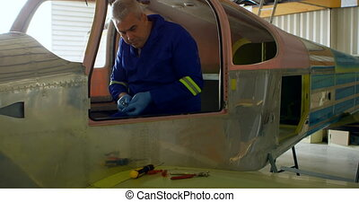 Engineer repairing aircraft in hangar 4k