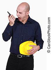 Engineer screaming into a walkie-talkie