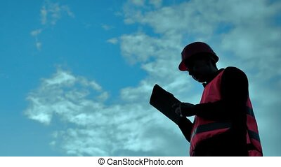 engineer silhouette holding yellow helmet works on a tablet...
