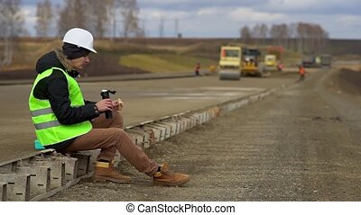 Engineer sitting on the road, eating a sandwich. Lunch...