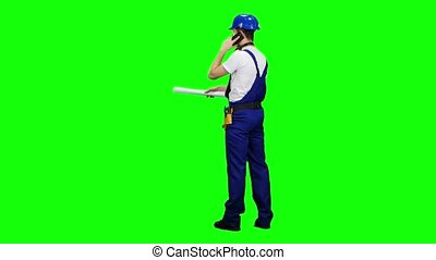 Engineer stands with his back to the drawing in his hands talking on the phone. Green screen